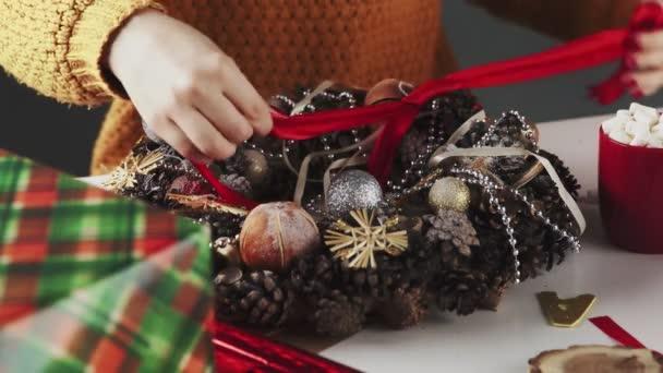 Unrecognizable Woman decorating Wreath Christmas On Table With Christmas Decoration.