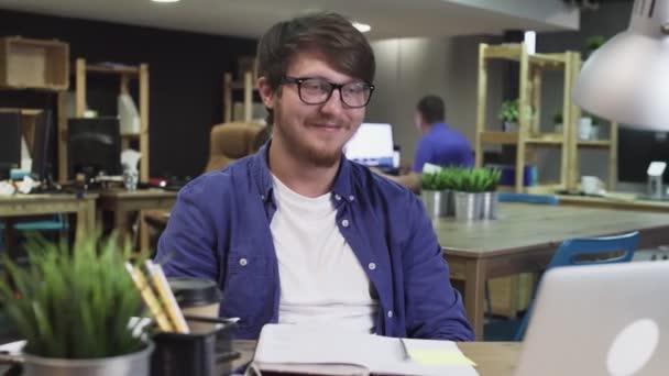 Mladý muž se dívá na legrační video v kanceláři