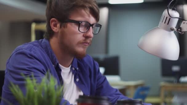 Seitenansicht eines Programmierers, der im Büro am Computer arbeitet