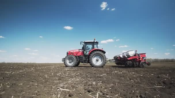 Tractor with special precision planters, seeder is working in the field, agricultural machinery is planting corn, or sunflower seed into freshly plowed land.