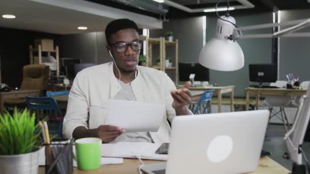 Afričan se sluchátky mají videokonferenční rozhovor v moderní kanceláři