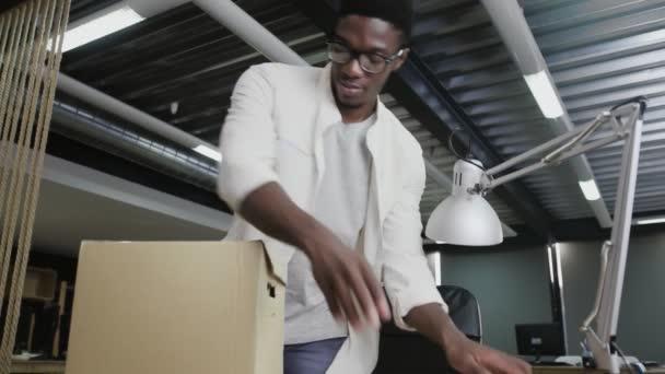 Egy afrikai férfi, akit nemrég vettek fel a céghez, új irodába jött. A férfi kipakolja a személyes holmiját.