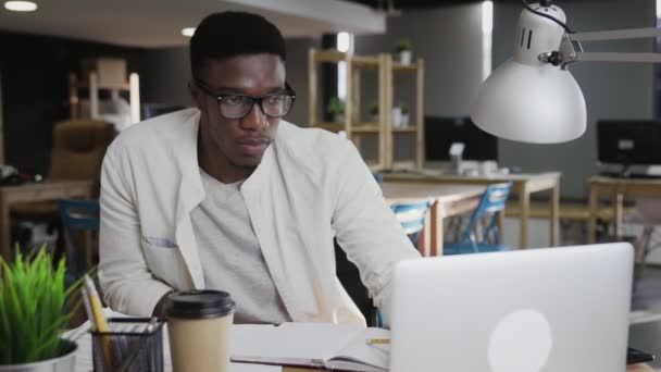Concentrated young african businessman writing and working on laptop in office