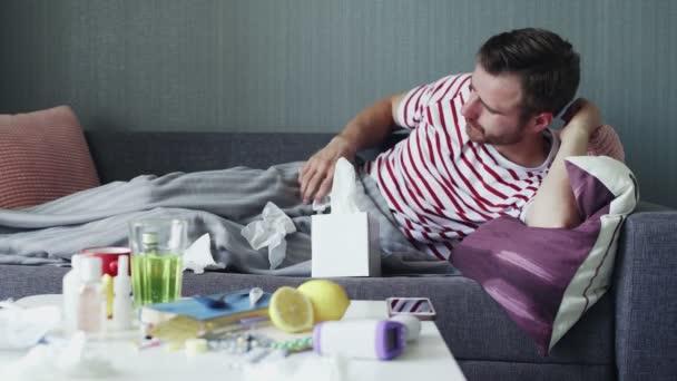 Ein kranker junger Mann versucht, während einer Krankheit auf einem Sofa in einer Wohnung unter einer warmen Decke einzuschlafen.
