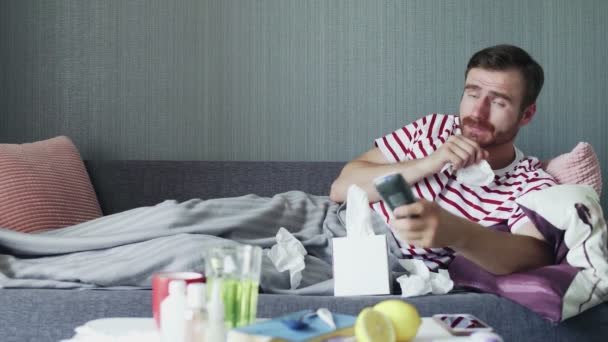 Sick man with flu at home, ill young man with fever watching tv show and using remote control.