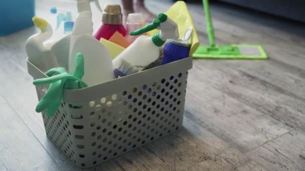 Koš plný houbiček a domácích chemikálií se ženou, která čistí podlahu mopem