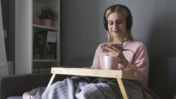 Mladá žena sedí na gauči jí tousty s čokoládovou pastou a sledovat video na smartphone