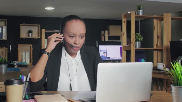 Naštvaná africká americká žena se sluchátky mluví se zákazníkem, zatímco se dívá na monitor počítače.