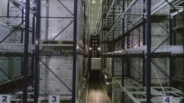 A dobozokat magas polcokon tárolják az ipari raktárban. Raktár kartondobozokkal raklaptartókon, logisztikai központ.