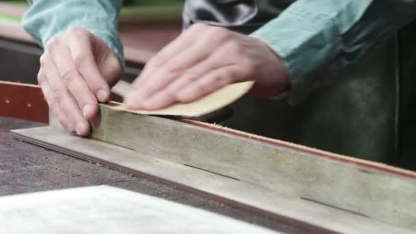 Ein Handwerker schärft gerade die Kanten eines Gürtels. Der Ledermeister bastelt einen Gürtel