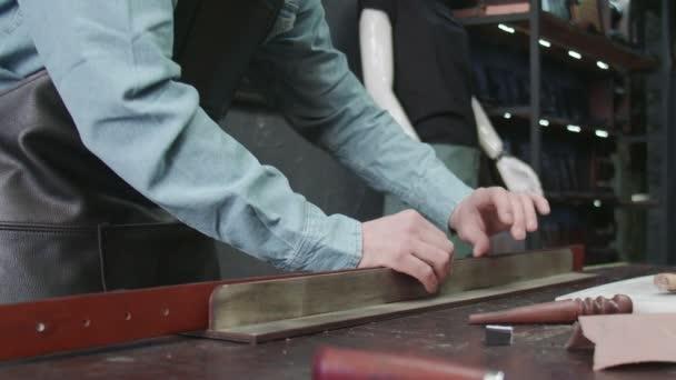 Der professionelle Gerber legt in der Werkstatt Kleister auf den Rand eines Bandes. Arbeitsprozess des Ledergürtels in der Lederwerkstatt.