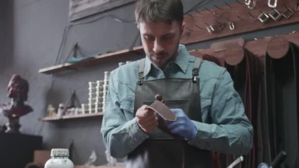 Professionelle Gerber reiben die Kanten eines Gürtels. Der Meister benutzt das Reibwerkzeug.