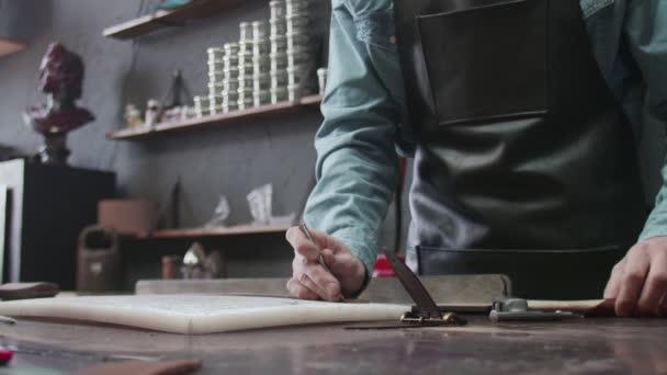 Professioneller Gerber mit Schürze fertigt in der Lederwerkstatt einen neuen braunen Ledergürtel an. Arbeitsprozess des Ledergürtels in der Lederwerkstatt.