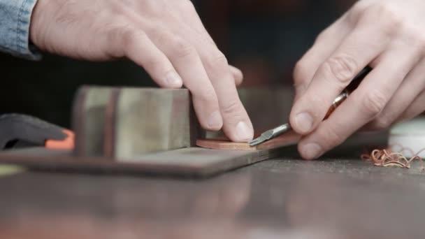 Ein Lederhandwerker schneidet die Kanten eines Gürtels. Der Meister verwendet ein Kantenanfaswerkzeug.