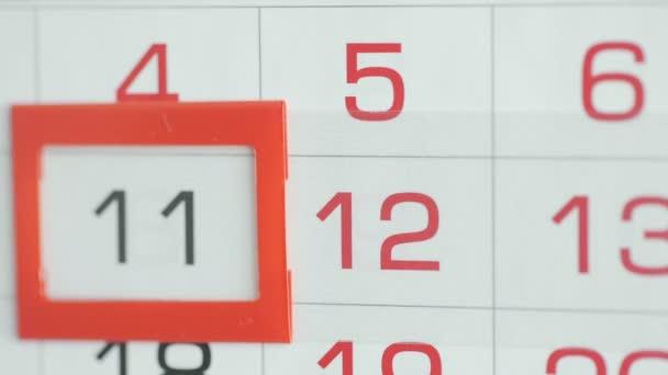 Ženy v kanceláři mění datum v kalendáři stěn. Změny 11 až 12