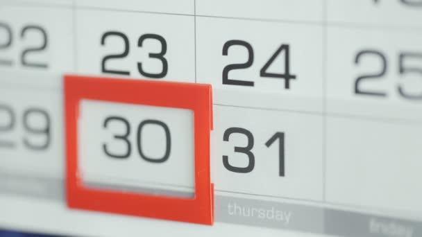 Ženy v kanceláři mění datum v kalendáři stěn. Změny 30 až 31