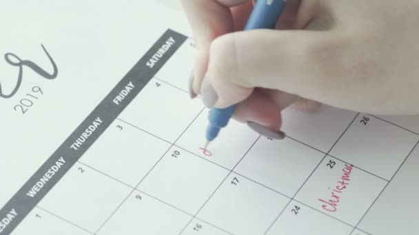 Macro of the hand writing a word deadline in the schedule under the date of 11
