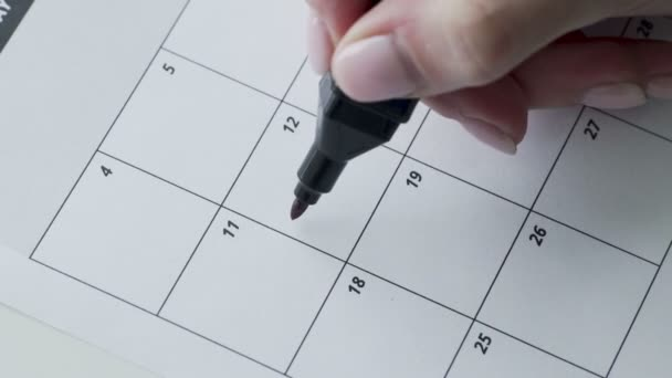 Womans hand writing with red felt pen on calendar word fitness