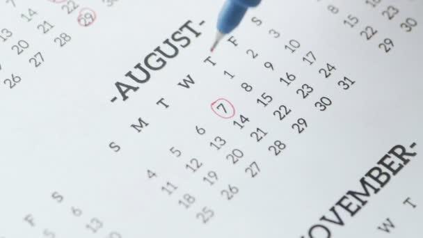 Dámský kruh v ruce 7. den v srpnu na papírovém kalendáři.