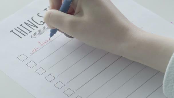 Junges Mädchen füllt To-do-Liste in Notizbuch.