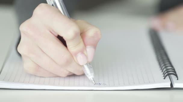 A nő tollal ír egy füzetben.