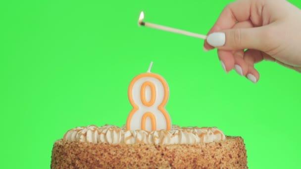 Meggyújtani egy 8-as számú szülinapi gyertyát egy finom tortán, zöld képernyő 8