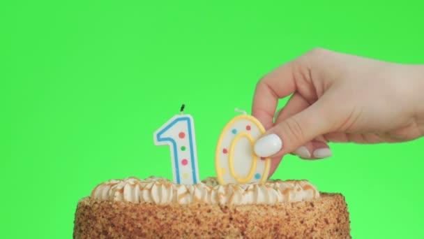 Dát číslo deset narozeninové svíčky na lahodný dort, zelená obrazovka 10