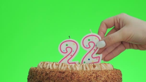 Dát číslo dvaadvacet narozeninové svíčky na lahodný dort, zelená obrazovka 22
