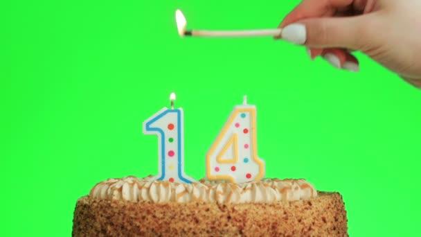 Meggyújtani egy tizennegyedik szülinapi gyertyát egy finom tortán, zöld képernyő 14