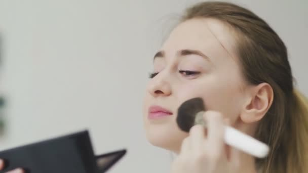 Woman Using Powder And Looking In Mirror