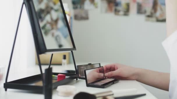 Žena nanášení make-upu pomocí štětce a palety kosmetiky