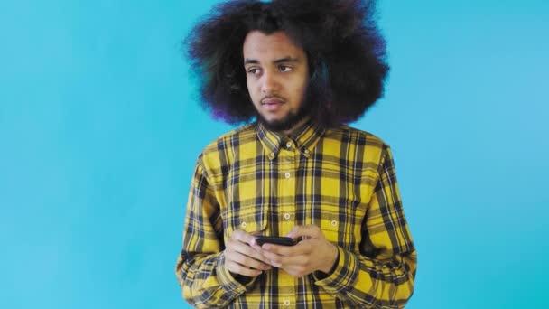Afroameričan s kudrnatými vlasy přemýšlí, než pošle zprávu na modré pozadí. Pojetí emocí