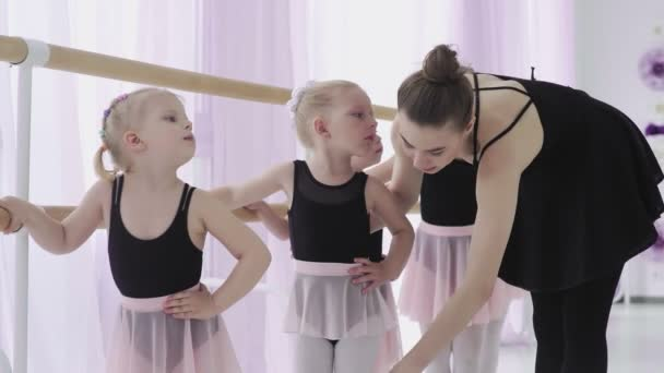 Group of little girls learning new dance moves during ballet lesson