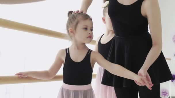 A woman and a girls in a ballet school. Adult ballerina practicing with the little girls and trains Russian classical ballet