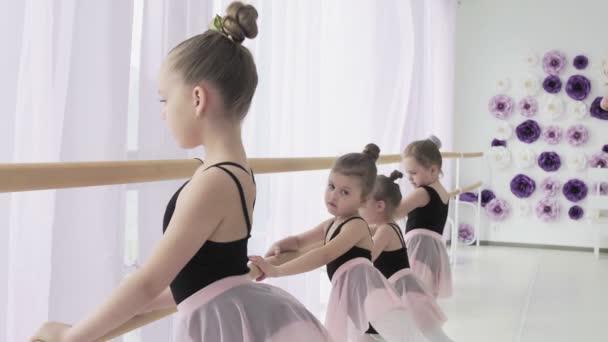 A szorgalmas fiatal balett-táncosok plie és battement tendut csinálnak, miközben a tanárnőjük rossz pozíciókat javít ki és utasításokat ad..