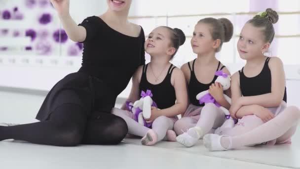 Aranyos Női balett tanár csinál szelfi vele kis diák okostelefon és pózol a kamera, miközben ül a tánctér padlóján szünet közben balett iskola.