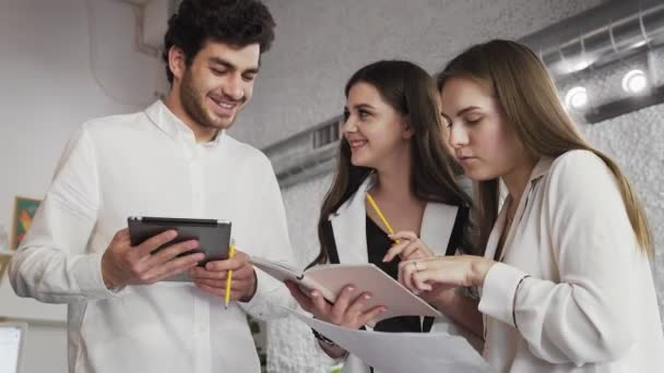 Three young corporate executives standing in lobby of modern building discussing business using digital tablet and notebook