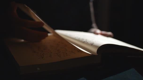 Jemand blättert im Dunkeln in alten Büchern