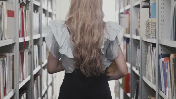 Zpět pohled blondýny studentka chůze mezi knihovnami v univerzitní knihovně s mnoha knihami v rukou