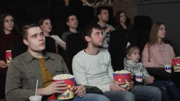 Die Leute essen Popcorn und schauen einen Film im Kino