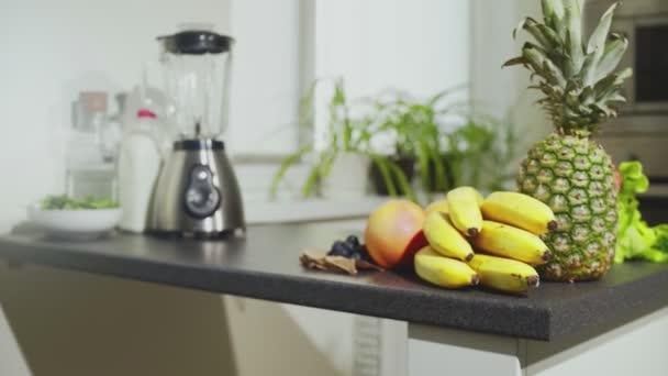 Friss gyümölcs és keverő az asztalon. Banán, alma, narancs, ananász és szőlő