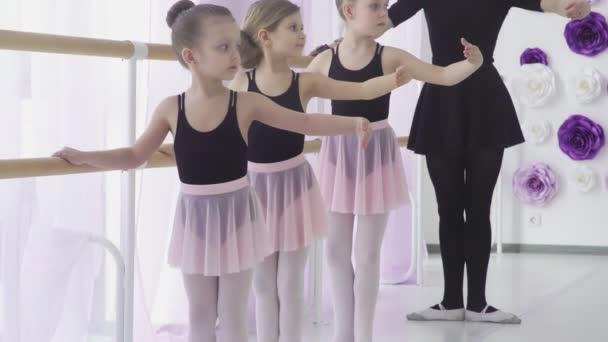 Kleine Mädchen lernen bei klassischem Ballettunterricht Beinbewegungen mit Lehrerin im Kunststudio.