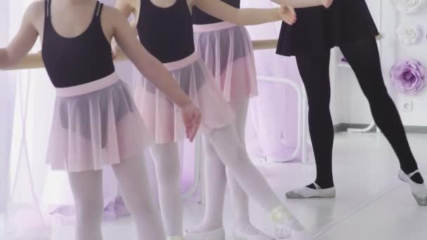 Little girls are having classical ballet lesson learning leg movements with teacher in art studio.