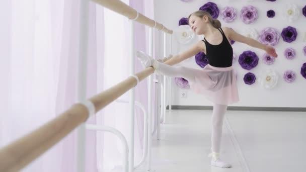 Fiatal balerina portréja a balettkorlát mellett a stúdióban.