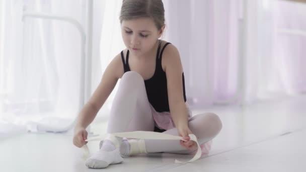 Nette Balletttänzerin bindet vor dem Training Ballettschuhe
