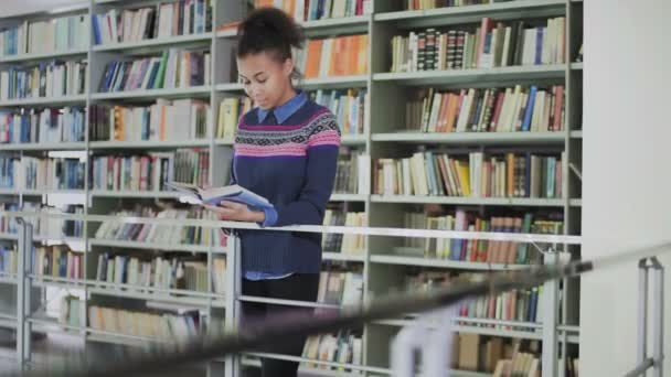 Portrait of the young curly African American woman reading the old book while standing near the books shelves in the library.