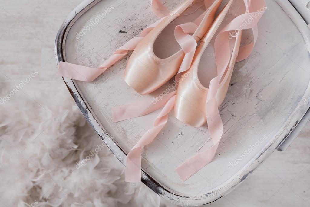 ae065bfd5a Sapatilhas de ballet rosa e penas no fundo de madeira branco — Fotografia  de Stock