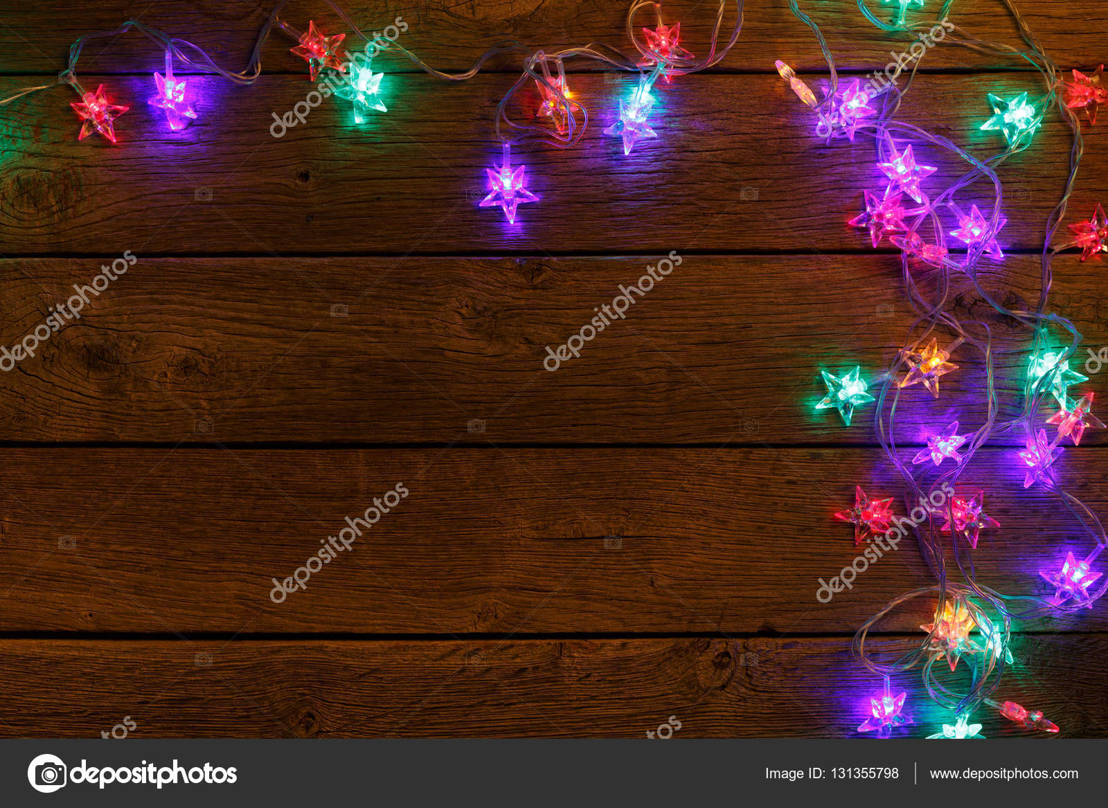 Christmas Lights Background Holiday Shiny Glowing Garland In Star Shape Border Top View With Copy Space On Light Brown Wooden Planks Surface