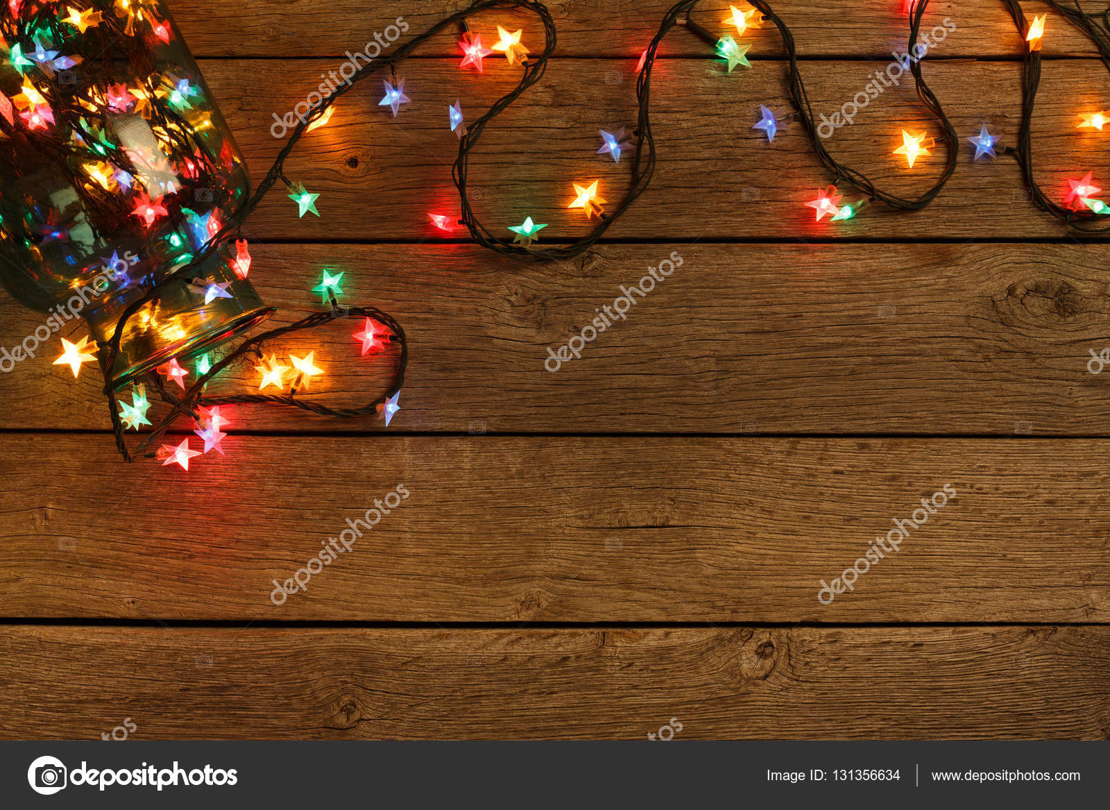 Christmas Lights Background Holiday Shiny Sparkling Star Garland Border Spread From Glass Jar Top View On Brown Wooden Planks Surface