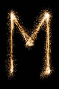 English Letter M from sparklers alphabet on black background.